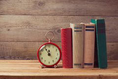 Vintage books and clock on wooden table Royalty Free Stock Images