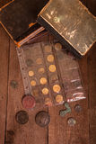 Vintage books and coins on old wooden table Stock Photography