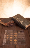 Vintage books and coins on old wooden table Royalty Free Stock Photo