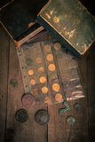 Vintage books and coins on old wooden table. Toned Stock Photography