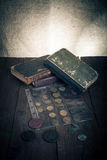 Vintage books and coins on old wooden table. Toned Royalty Free Stock Images