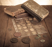 Vintage books and coins on old wooden table. Toned Stock Photo