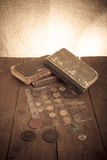 Vintage books and coins on old wooden table. Toned Stock Images