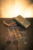 Vintage books and coins on old wooden table. Toned Stock Image