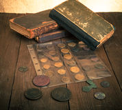 Vintage books and coins on old wooden table. Toned Stock Photos