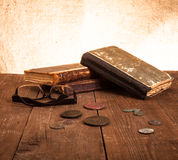 Vintage books and coins and spectacles on old wooden table. Tone Royalty Free Stock Images