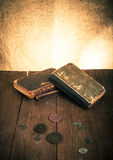 Vintage books and coins and spectacles on old wooden table. Tone Stock Images