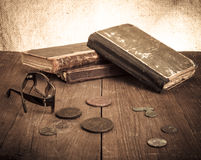 Vintage books and coins and spectacles on old wooden table. Tone Stock Photos