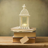 Vintage books and decorative lantern on wooden table. Christmas celebration Stock Photos