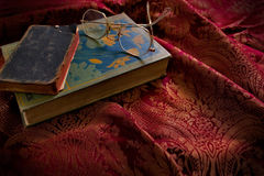 Vintage Books with Glasses. Resting on top sitting on old red and gold fabric Stock Photography