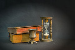 Vintage books and hourglass. In dark room royalty free stock photography