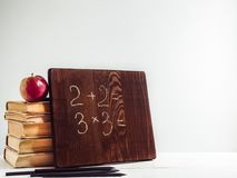 Vintage books, old clock, pencils, red apple and blackboard. With a handwritten inscription on a wooden, white table. Close-up, isolated. Back to school stock photo