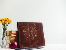 Vintage books, old clock, pencils, red apple and blackboard. With a handwritten inscription on a wooden, white table. Close-up, isolated. Back to school stock image