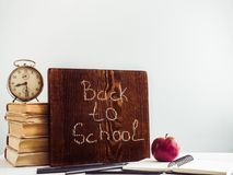 Vintage books, old clock, pencils, red apple and blackboard. With a handwritten inscription on a wooden, white table. Close-up, isolated. Back to school royalty free stock photo
