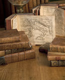 Vintage books old maps on a wooden table. Vintage books with old maps standing in a row on a wooden table Royalty Free Stock Image