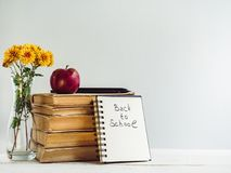 Vintage books, pencils, notepad with a handwritten inscription. And an apple on a wooden, white table. Close-up, isolated. Back to school royalty free stock photo