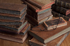 Vintage books and reading glasses. Vintage books are stacked on a wooden table with a pair of reading glasses on top Royalty Free Stock Photo