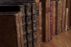Vintage books in a row. Vintage books and maps standing in a row on a wooden table Royalty Free Stock Images