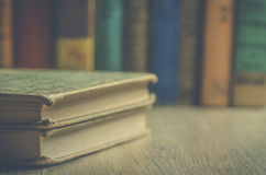 Vintage books on a wooden bookshelf with books in background. Image of old books stacked in  a pile on wooden bookshelf Stock Images