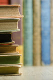 Vintage books on a wooden bookshelf with books in background. Image of old books stacked in  a pile on wooden bookshelf Stock Photo