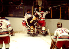 Vintage Boston Bruins v. New York Rangers. Johnny Bucyk #9,  goes into the corner to dig the puck up against Gary Doak #3 pins Phil Esposito against the boards Royalty Free Stock Image