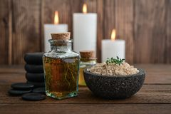 Spa concept. Vintage bottle with masssage oil, candles and stones for stone massage on wooden background Stock Photos