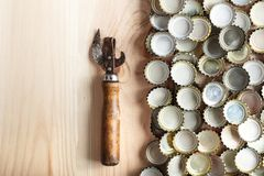 Vintage bottle opener. Vintage Opener near the lid of beer, on a wooden background, space for text Stock Photo