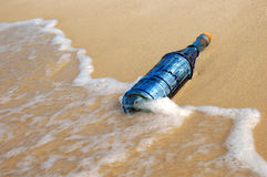 Vintage Bottle and Waves. Vintage bottle with a message on the shore and waves Stock Image