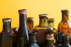 Vintage bottles close-up. Colorful dirty glass flacon set. Soft yellow orange background, shallow depth of field. Royalty Free Stock Images