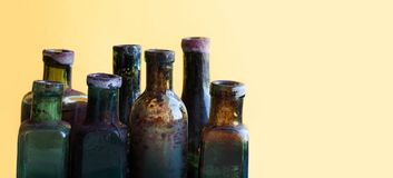 Vintage bottles close-up. Colorful dirty glass flacon set. Soft yellow orange background, shallow depth of field. copy Royalty Free Stock Image