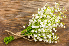 Vintage bouquet of wild flowers, the white scented lilies of the valley on an old wooden plank Stock Photo