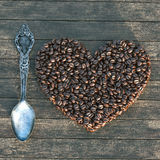 Vintage box with spoon and heart shape coffee beans. On a wooden table. 3D render Royalty Free Stock Images