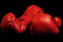 Vintage boxing gloves emerging from black background Royalty Free Stock Photos