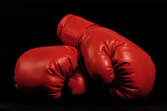 Vintage boxing gloves emerging from black background Royalty Free Stock Images