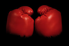 Vintage boxing gloves emerging from black background Stock Image