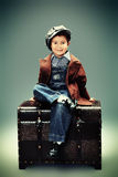 Vintage boy. Portrait of a cute little boy sitting with a huge old trunk. Vintage style Stock Photography