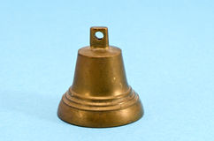 Vintage brass bell on blue background Royalty Free Stock Image
