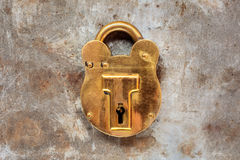 Vintage brass padlock on a steel rusty background Stock Photo