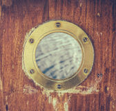 Vintage Brass Porthole With Ocean Water Stock Images