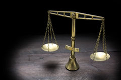 Vintage brass scales of justice in spotlight against a black bac Royalty Free Stock Photography