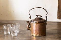 Vintage brass tea pot with empty glasses Stock Photo