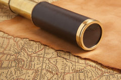 Vintage brass telescope. On antique map Royalty Free Stock Images