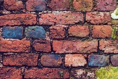 Vintage brick wall background with spotlights on the wall in heart shape. Multi-colored bricks in the old wall close-up. Background in grunge style stock photography