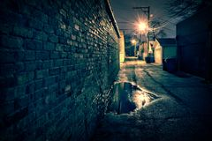 Vintage brick wall in a dark and wet Chicago alley at night. stock images