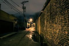 Vintage brick wall in a dark, gritty and wet Chicago alley. At night after rain Royalty Free Stock Photos