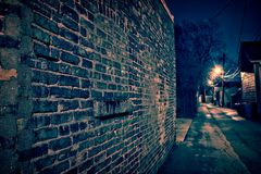 Vintage brick wall in a dark and wet Chicago alley at night. Vintage brick wall in a dark, gritty and wet Chicago alley at night after rain Stock Image