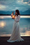 Vintage bride on lake pier with lantern Stock Photo