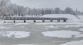 Vintage bridge over the frozen pond. Winter in Europe. Klaipeda, Lithuania Stock Photography
