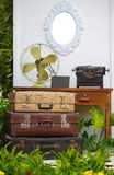 Vintage briefcase and fan in a garden setting Royalty Free Stock Photo