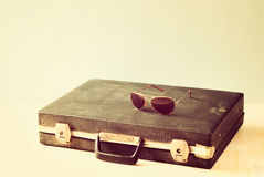 Vintage briefcase and glasses over wooden shelf. vintage filter. Stock Photos